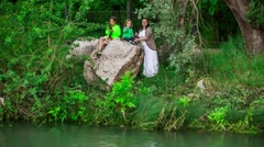Mother And Two Children Throwing Stones Into Pond Stock Footage