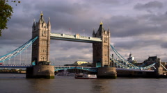 Ship passes under Tower bridge with dark clouds in distance in London, England. Stock Footage