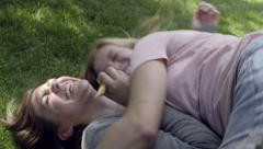 Girl Eats A Pretzel, Her Friend Hugs Her, Another Friend Piles On Top Of Them Stock Footage