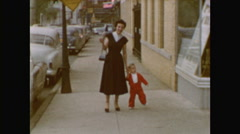Glam Mom and little boy walk down city street Stock Footage