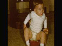 Baby boy in diaper sits in antique highchair Stock Footage