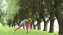 Young slender woman practicing yoga in a city park. Dolly shot. - stock footage
