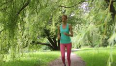 Young slender woman jogging in a city park. Dolly shot. Stock Footage