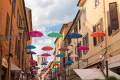 Ancient medieval street in the downtown of Ferrara city with umbrellas Stock Photos