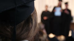 Girl in academic cap looking at students receiving diplomas, college graduation - stock footage