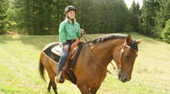 Young girl riding a horse in a meadow Stock Footage