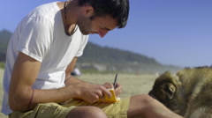Young man writes in his journal sitting on the beach with his dog Stock Footage