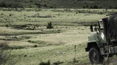 Truck driving across field down hill. Stock Footage
