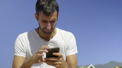 Young man using his cell phone on the beach Stock Footage