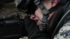 Close-up moving from a soldier's face to his hand pulling the trigger. Stock Footage