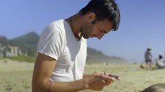 Man sending text messages sitting in the sand at the beach. - stock footage