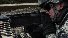 Close-up of a soldier's firing a belt-fed machine gun. Stock Footage