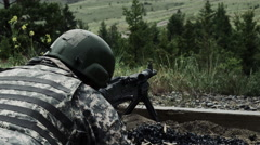 View from over the shoulder of a soldier as he is shooting a belt-fed machine Stock Footage
