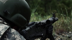 Close view over the shoulder of a soldier as he shoots a belt-fed machine gun. Stock Footage