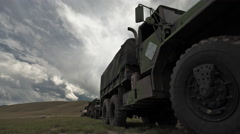 Dollying time-lapse of a stationary military convoy truck. - stock footage