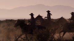 Cowboy rides from camera right to camera left, then 3 more follow Stock Footage