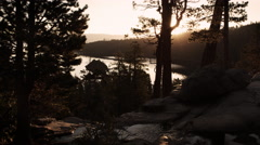 Dark shot of sun peaking through trees over water and��stream near Lake Tahoe, Stock Footage