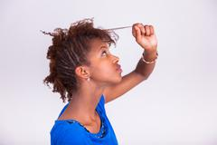 Young African American woman holding her frizzy afro hair - Black people Stock Photos