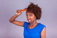 Young African American woman combing her frizzy afro hair - Black people Stock Photos