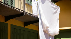 Clean bed sheets hanging outside to dry in the sun in front of garages Stock Footage
