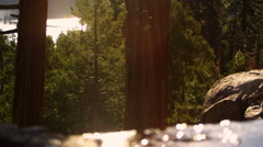 Shot of a brook, rocks and trees in a forest with Lake Tahoe in the background. Stock Footage