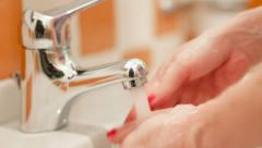 Woman washing her hands at the sink in colorful bathroom Stock Footage