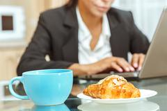 Businesswoman with cup of coffe and croissant - stock photo