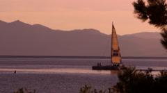 Sailboat at dusk. Shot at Emerald Bay State Park, Lake Tahoe, California Stock Footage