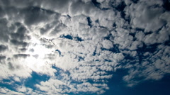 Clouds moving in the blue sky on the background of the bright sun Stock Footage