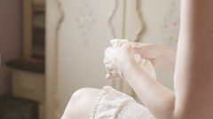 Bride pulling up stockings getting ready for her wedding - back shot Stock Footage