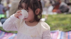 Portrait of young Japanese girl drinking from a paper cup in a city park - stock footage