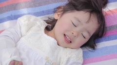 Portrait of young Japanese girl playing on a leisure sheet in a city park Stock Footage