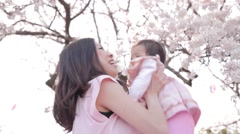 Japanese young mother and daughter enjoying in a city park Stock Footage