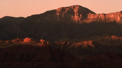 Distant shot of night falling over red mountains Stock Footage