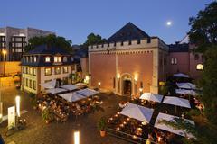 Restaurant terraces in front of the HeiligGeistSpital hospital dusk Mainz - stock photo