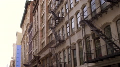 Tracking shot of the side of buildings with fire escapes. Stock Footage