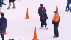 Slow motion panning shot of ice skaters on the Central Park ice rink. Stock Footage