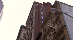 Dolly shot looking up at tall, old apartment buildings in New York City. - stock footage