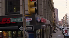 Panning, dolly shot of businesses on Broadway in New York City. Stock Footage