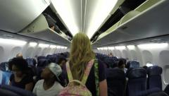 4K POV following young woman down airplane aisle Stock Footage