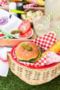 Small summer picnic with lemonade and hamburgers in the park. - stock photo