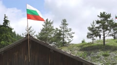 Bulgarian flag is shaken by the wind on a wooden house in the mountains Stock Footage