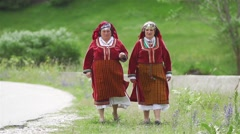 Two grandmothers in Bulgarian folk costumes walk the lawn in slow motion Stock Footage