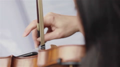 Playing violin with fingers. Female hand plucking strings of violin. Close up - stock footage