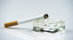 Stock Video Footage of Lit cigarette in an ashtray close up.
