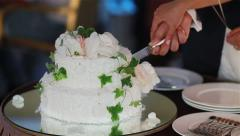 Newlyweds hands cutting white wedding cake to pieces. Close up Stock Footage
