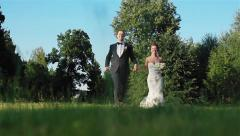 Smiling happy newlyweds couple holding hands run together in green meadow Stock Footage