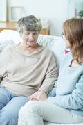 Female senior talking with caregiver - stock photo