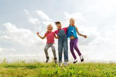 Group of happy kids jumping high on green field Stock Photos