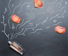 fragrance bottle with drowing smell androse petal on the blackboard - stock photo